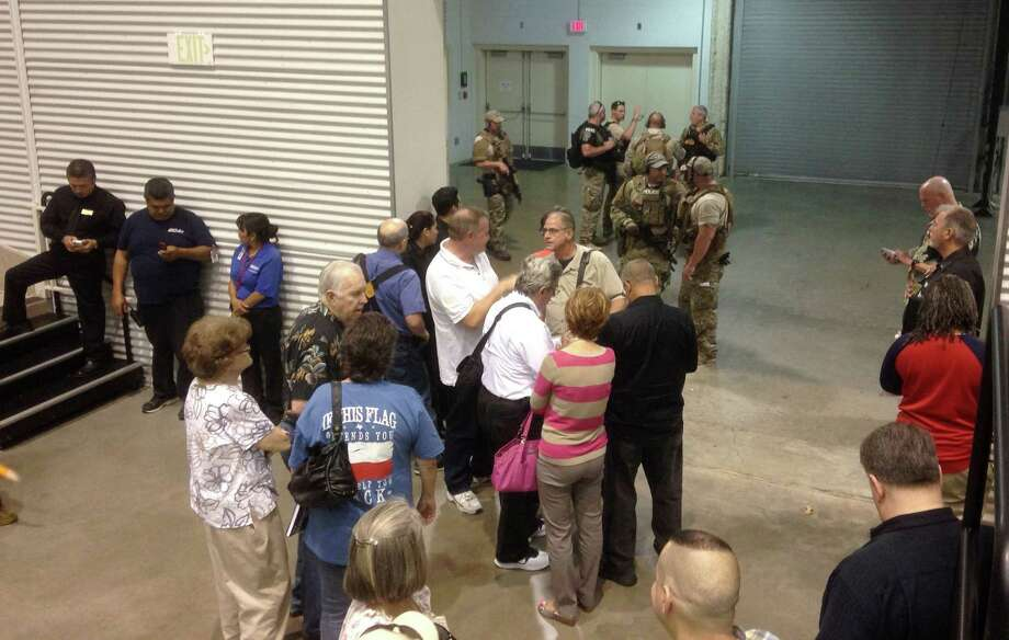 People are sequestered by members of the Garland Police Department inside the Curtis Culwell Center on May 3, 2015 in Garland, Texas. A contest for cartoons depictions of the Prophet Muhammad in the Dallas suburb is on lockdown Sunday after authorities reported a shooting outside the building. Photo: AP Photo/Nomaan Merchant   / AP