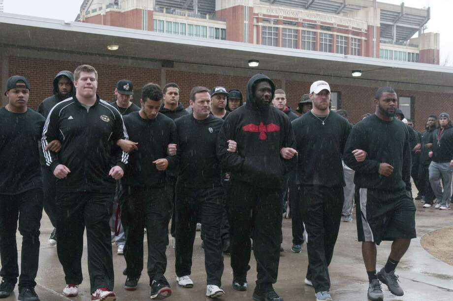 The University of Oklahoma football team and coaches line up wearing all black in the Everest Training Center in protest of the Sigma Alpha Epsilon fraternity at the University of Oklahoma on March. Photo: AP Photo   / Tulsa World