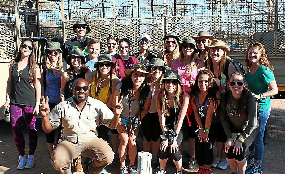 Quinnipiac University students and staff take a photo with an unidentified tour guide during their trip to Lion Park in Johannesburg, South Africa. Photo: Contributed Photo / Peter Gallay ©2015