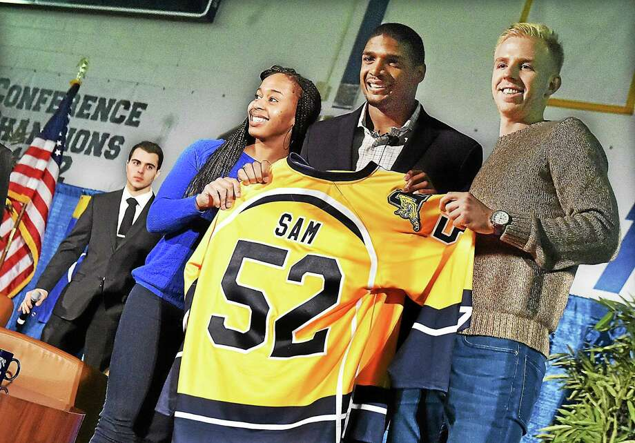 Quinnipiac University senior and basketball player Jasmine Martin, of Sickleville, New Jersey, and Tobias Esche, a junior and captain of the soccer team, present Michael Sam with a Quinnipiac University hockey jersey. Photo: Catherine Avalone — New Haven Register   / New Haven RegisterThe Middletown Press