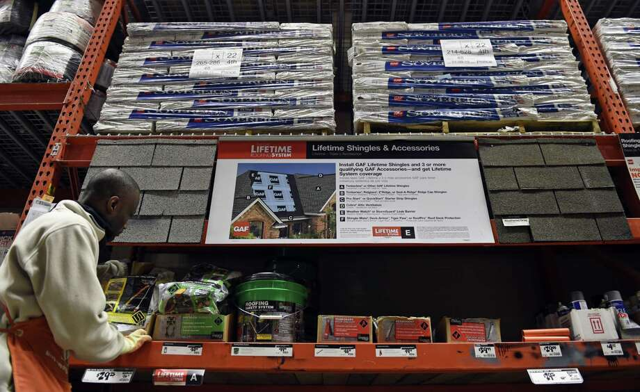 In this Feb. 23, 2015 photo, Prince Addy of Manassas, Va., straightens up the shelves of roofing products at the Home Depot in Falls Church, Va. A harsh winter has taken a toll on many roofs around the country. The first step in roof maintenance may be to get out a pair of binoculars and take stock. Photo: AP Photo/Susan Walsh   / AP