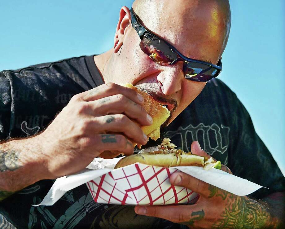 A festival-goer takes a bite out of a grinder at the first-ever New Haven Food Truck Festival on Long Wharf May 30. Photo: Catherine Avalone — New Haven Register   / New Haven RegisterThe Middletown Press