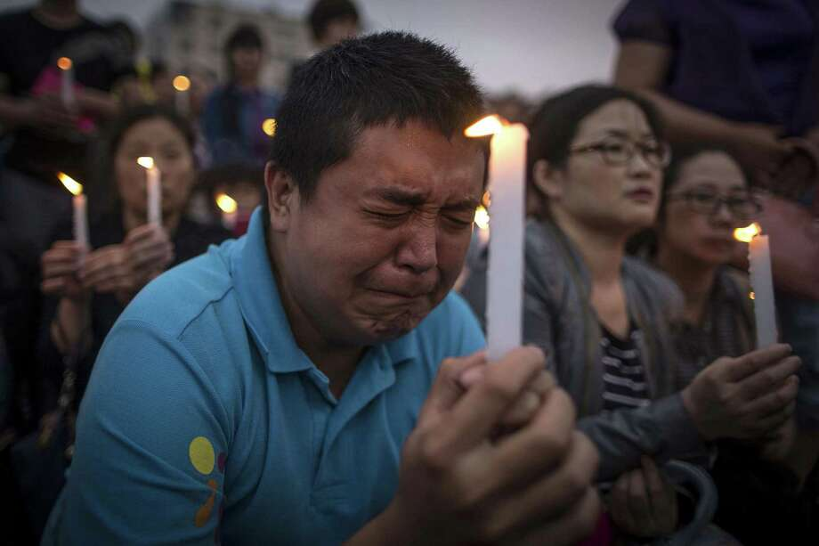A man reacts during a candle light vigil by locals and family members of passengers onboard the capsized cruise ship in Jianli county in southern China's Hubei province Thursday. Rescuers cut three holes into the overturned hull of a river cruise ship in unsuccessful attempts to find more survivors. Photo: Chinatopix Via AP   / CHINATOPIX