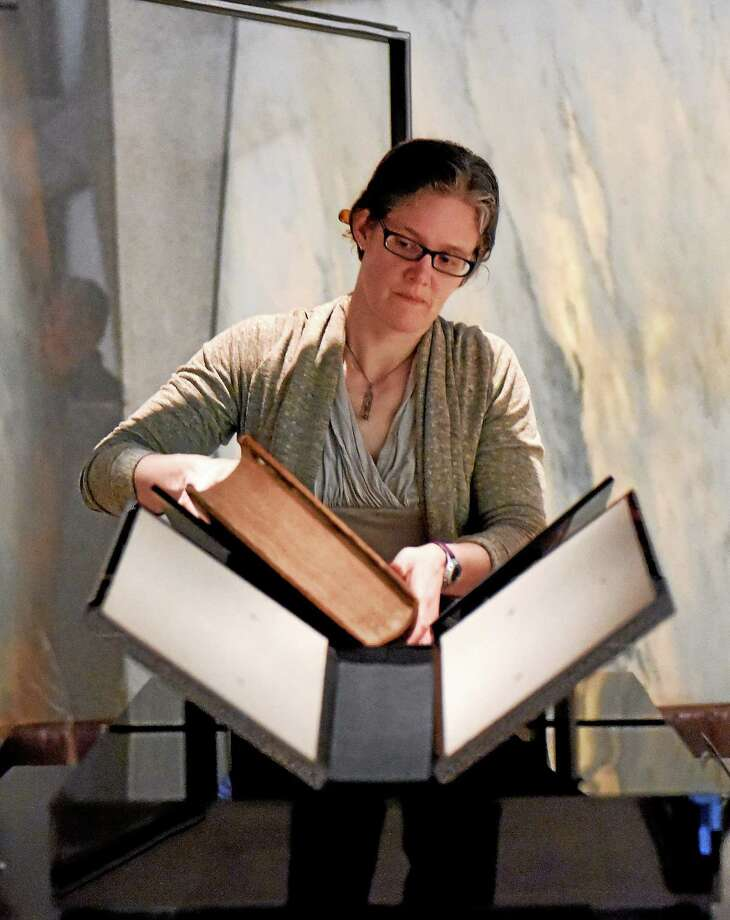 Rebecca Hatcher, the preservation coordinator librarian at the Beinecke Rare Book and Manuscript Library, removes the two-volume Gutenberg Bible from its locked and alarmed glass enclosure, swaddling it in a protective plastic box for the trip to Chapel Street. Photo: Peter Hvizdak — New Haven Register    / ?2015 Peter Hvizdak