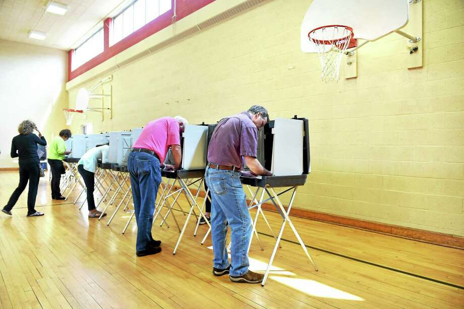 Jeffrey Hague, center, votes in the Woodbridge election at Center School gymnasium Monday. Photo: Arnold Gold — New Haven Register