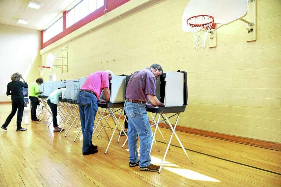 Jeffrey Hague, center, votes in the Woodbridge election at Center School gymnasium Monday. Photo: Arnold Gold — New Haven Register