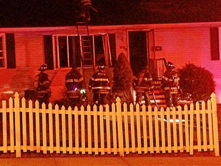 City firefighters battled flames Wednesday night in the basement of a home at 95 Pond Lily Ave. in Amity. Photo: Photo Courtesy Of Brad Young.