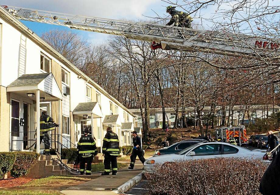 City firefighters clean up and investigate after dryer fire broke out at a New Haven apartment complex Friday afternoon. No one was injured in the incident, but at least one tenant was displaced from a unit. Photo: (Wes Duplantier -- New Haven Register)