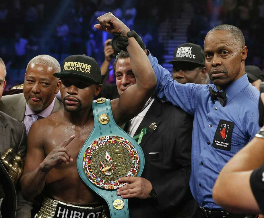 Floyd Mayweather Jr., left, holds up the title belt next to referee Kenny Bayless after his win against Manny Pacquiao on Saturday in Las Vegas. Photo: John Locher — The Associated Press   / AP