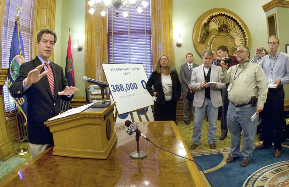 Gov. Sam Brownback meets with the media on May 30 in Topeka, Kan. Brownback is proposing a state sales tax increase and other measures to deal with the state's projected budget shortfall. Photo: The Topeka Capital-Journal Via AP   / TOPEKA CAPITAL-JOURNAL