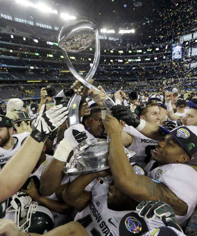 Michigan State players hoist the trophy after they beat Baylor 42-41 in the Cotton Bowl on Thursday in Arlington, Texas. Photo: LM Otero — The Associated Press   / AP