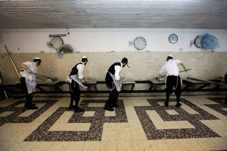 Ultra-orthodox Jews prepare special matzoh, a traditional handmade Passover unleavened bread, at a bakery in Jerusalem, Wednesday, April 1, 2015. Jews are forbidden to eat leavened foodstuffs during the Passover holiday, which celebrates the biblical story of the Israelites' escape from slavery and exodus from Egypt. (AP Photo/Sebastian Scheiner) Photo: AP / AP