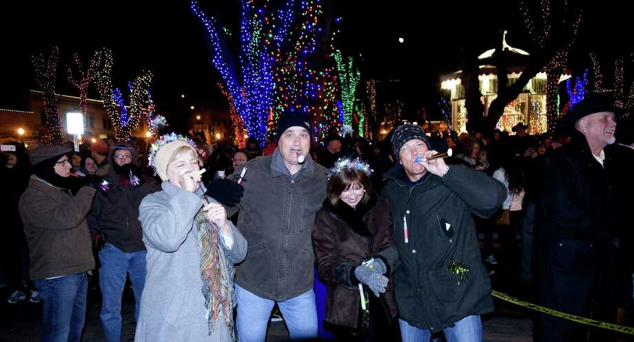 In this Dec. 31, 2013 photo, people cheer and celebrate New Year's Eve during the annual Boot Drop on Whiskey Row in downtown Prescott, Ariz. Televised images every year of New York Cityís glittery ball drop in Times Square have become inextricably linked with New Yearís Eve. But Times Square isnít the only place to ring in the new year with an object dropping from the sky at midnight. (AP Photo/The Daily Courier, Les Stukenberg) Photo: AP / The Daily Courier