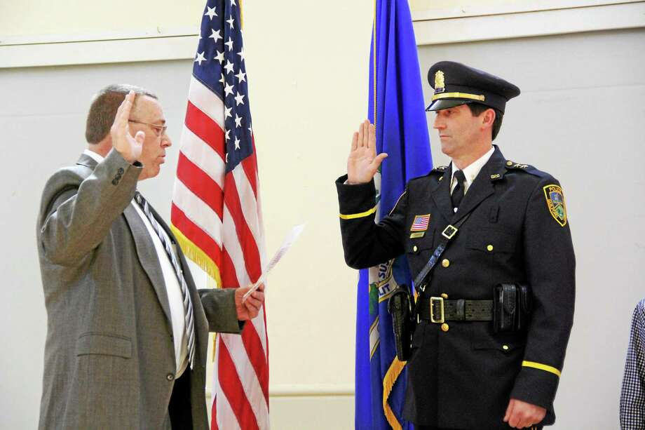 Chairman of the Police Commission Jeffrey Hedberg swears-in Jeffrey Hutchinson as Guilford's new police chief. Photo: Contributed Photo — Guilford POLICE Sgt. Timothy Bernier