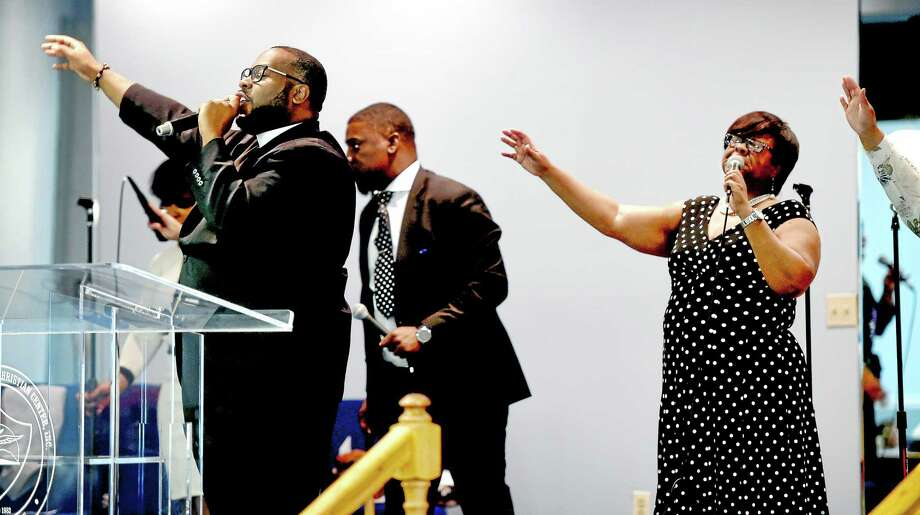 Cory Salsbury, left, leads parishioners in song at the Agape Christian Center in New Haven Sunday before Mayor Harp and  Chief Esserman spoke to the congregation. Photo: Arnold Gold--New Haven Register