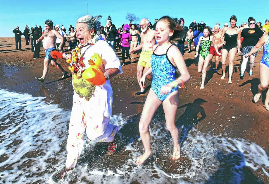 Liz Duckrow, center left, of New Haven leads the charge into Long Island Sound for the annual Polar Plunge at Lighthouse Point Park in New Haven Thursday. Photo: Arnold Gold — New Haven Register