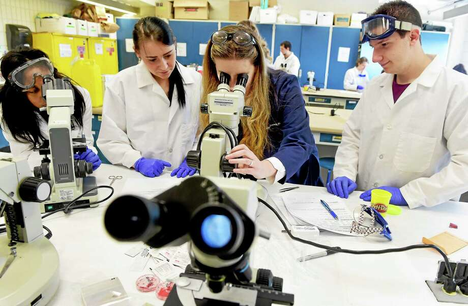 Dr.  Brooke Kammrath, a professor of forensic science at the University of New Haven prepares a specimen of automotive paint for viewing under a microscope Friday, April 24, 2015 during Criminal Juistice class that studies the identification, individualization, evaluation and reconstruction of physical evidence. With Kammrath, left to right are students Taneesha Thomas of Stratford, Amina Kunovac of New Jersey, and Bryan Bennica of Northford. Photo: Peter Hvizdak - New Haven Register   / ©2015 Peter Hvizdak