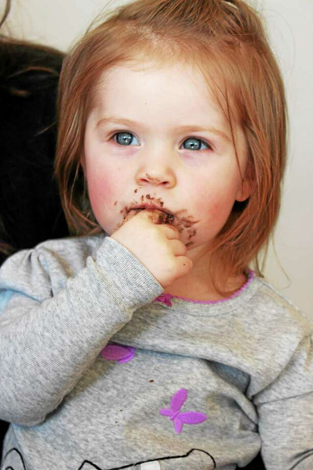 A fan shows cupcake enjoyment on her face. Photo: Journal Register Co.