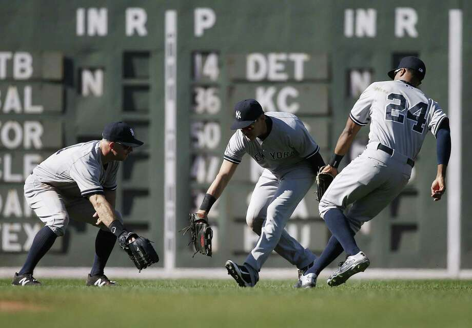 New York Yankees outfielders, from left, Jacoby Ellsbury, Brett Gardner and Chris Young celebrate after defeating the Red Sox 4-2 on Saturday afternoon in Boston. Photo: Michael Dwyer — The Associated Press   / AP