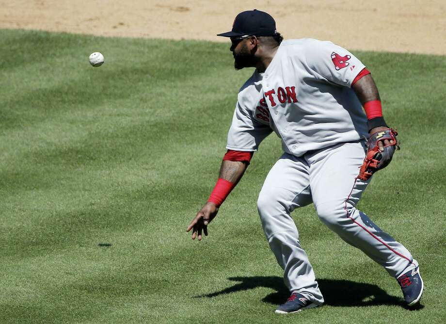 Boston Red Sox third baseman Pablo Sandoval mishandles the ball while attempting to throw to first during Sunday's game against the Rangers in Arlington, Texas. Photo: Brandon Wade — The Associated Press   / FR168019 AP