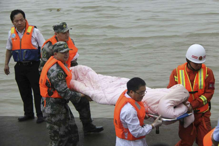 Rescue workers carry a survivor from the hull of a capsized cruise ship on the Yangtze River in Jianli in central China's Hubei province on June 2, 2015. Divers on Tuesday pulled survivors from inside the overturned cruise ship, state media said, giving some small hope to an apparently massive tragedy. Photo: Chinatopix Via AP   / CHINATOPIX