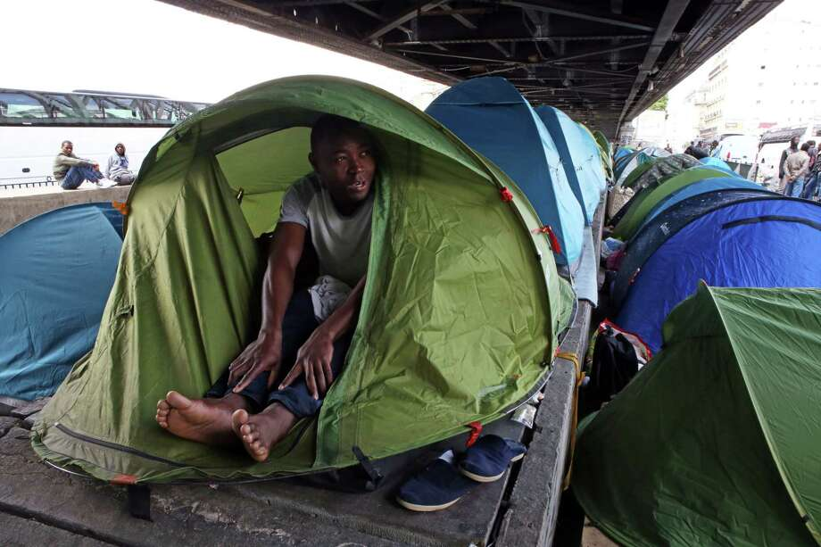 In this photo taken Monday, May 25, 2015, Mandela Drame, from Ivory Coast, speaks with The Associated Press as he sits in his tent placed alongside dozens of others set up by migrants under a metro bridge near the Gare du Nord station in Paris, France. Hundreds of migrants, mostly from east Africa, have poured into the ersatz tent camp on the bridge under a rumbling subway line and over tracks that take Eurostar trains to Britain. (AP Photo/Remy de la Mauviniere) Photo: AP / AP