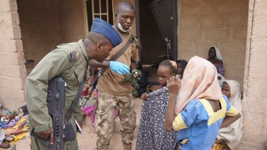 In this photo made available by the Nigerian Military taken Wednesday, April 29, 2015, a Nigerian soldier speaks to woman and children that were allegedly rescued by the Nigerian Military after being taken by Islamic extremists in Sambisa Forest, Nigeria. Scores more women and children have been rescued from Islamic extremists in the remote Sambisa Forest, Nigeria's military said amid reports that some of the women fought their rescuers fiercely. Photo: (Nigerian Military Via AP) / Nigeria Military