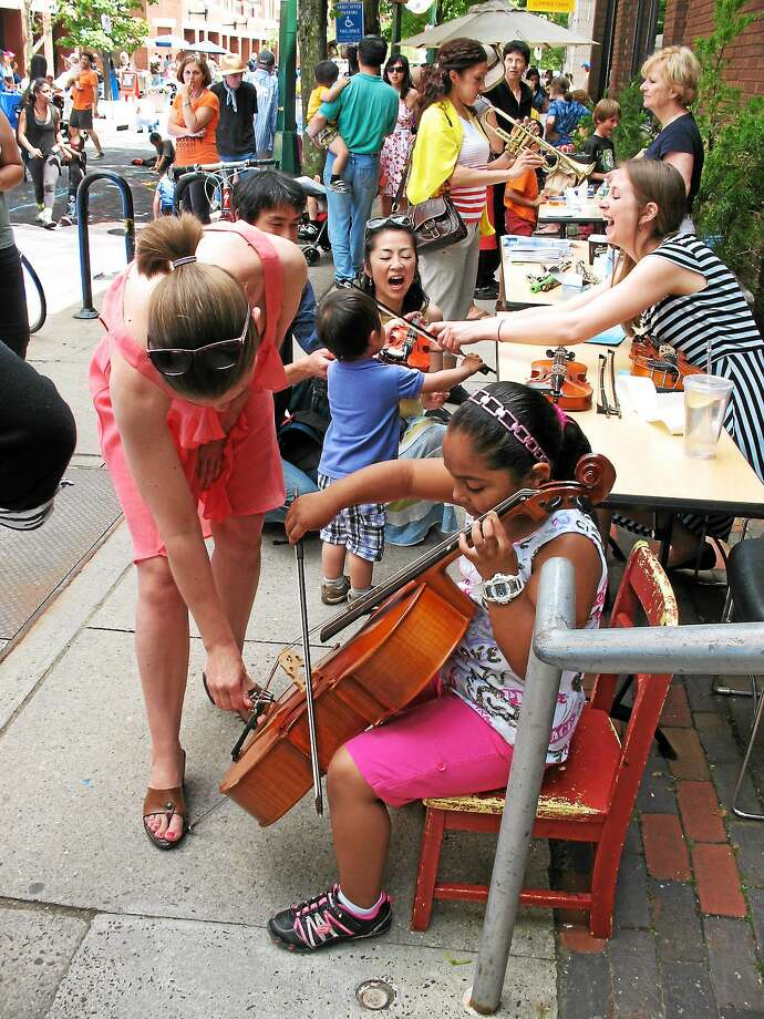 Neighborhood Music School staffers help students in the instrument petting zoo area last year. Photo: Contributed