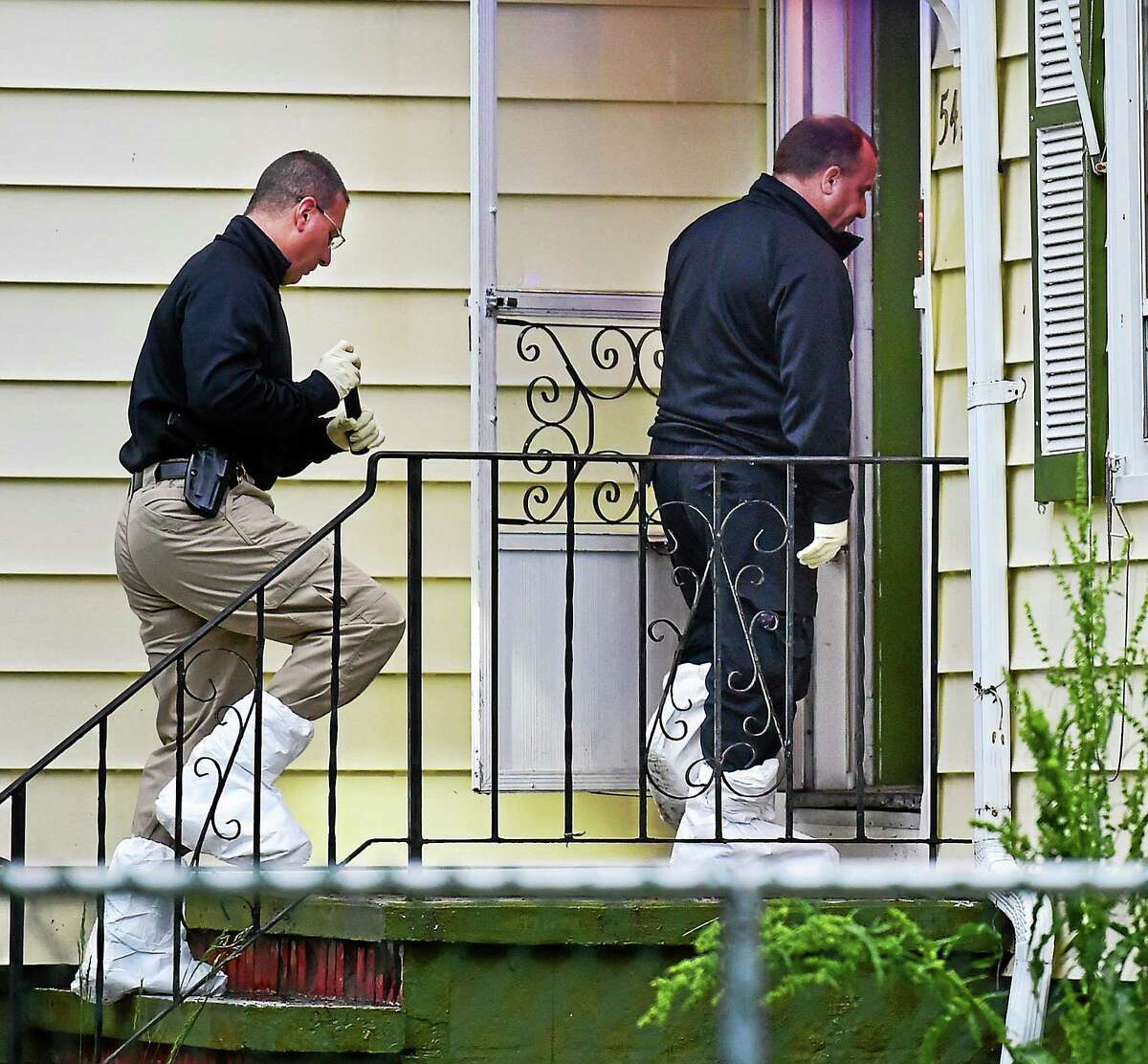 Members of the Connecticut State Police Major Crime Squad enter the home at 541 Strong St. in East Haven Tuesday, where two young children were found dead.