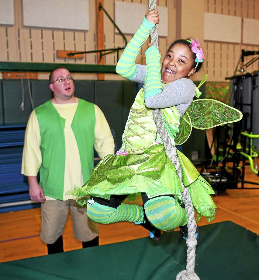 (Arnold Gold-New Haven Register)  Gym teacher Quentin Kaczmarek (left) as the Giant watches Madisyn Dukes, 8, dressed as Tinker Bell attempt to climb the beanstalk in the gymnasium of Wintergreen Interdistrict Magnet School in Hamden during Fairy Tale Day on 4/1/2015.  The gymnasium was transformed into the Magic Kingdom. Photo: Journal Register Co.