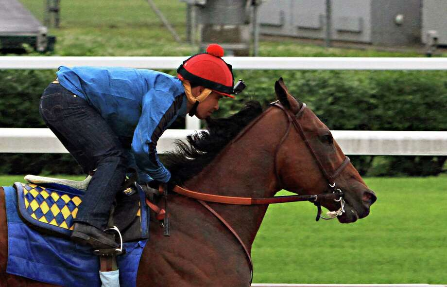 Triple Crown hopeful American Pharoah, ridden by jockey Martin Garcia, powers through his final timed workout in a steady, light rain at Churchill Downs on Monday. Photo: Garry Jones — The Associated Press   / FR50389 AP