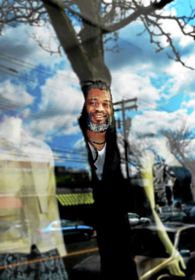 Neville Wisdom, owner of Neville Wisdom, a Jamaican-born fashion designer,  operates two retail shops and one showroom in the New Haven area.  Wisdom, a manufacturer of custom made clothing, is reflected in the window of his  Westville shop in New Haven Wednesday, April 24,  2015. Photo: (Peter Hvizdak - New Haven Register)   / ©2015 Peter Hvizdak