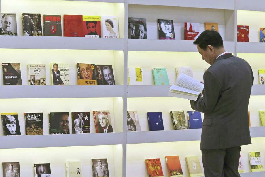 A visitor inspects books on display at the China pavilion at BookExpo America, Wednesday in New York. The convention floor's largest presence at BookExpo, covering some 23,000 square feet, is China, this year's featured foreign publishing industry. Photo: AP Photo   / AP