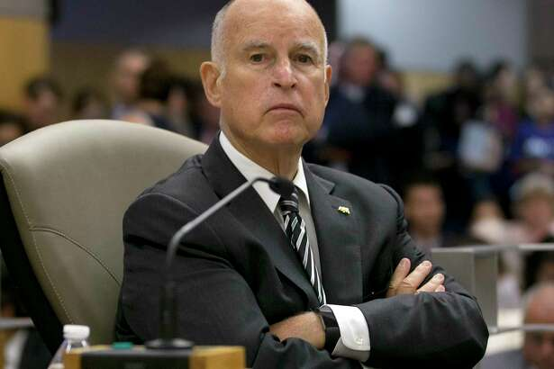 FILE -- In this July 13, 2017 file photo California Gov. Jerry Brown listens as members of the Senate Environmental Quality Committee discuss a pair of climate change bills he supports, in Sacramento, Calif. As his fourth and final term winds down Brown will spend the final 17 months in office working on California's housing crisis and fighting for ambitious projects to build a high-speed rail system and re-engineer California's water system.