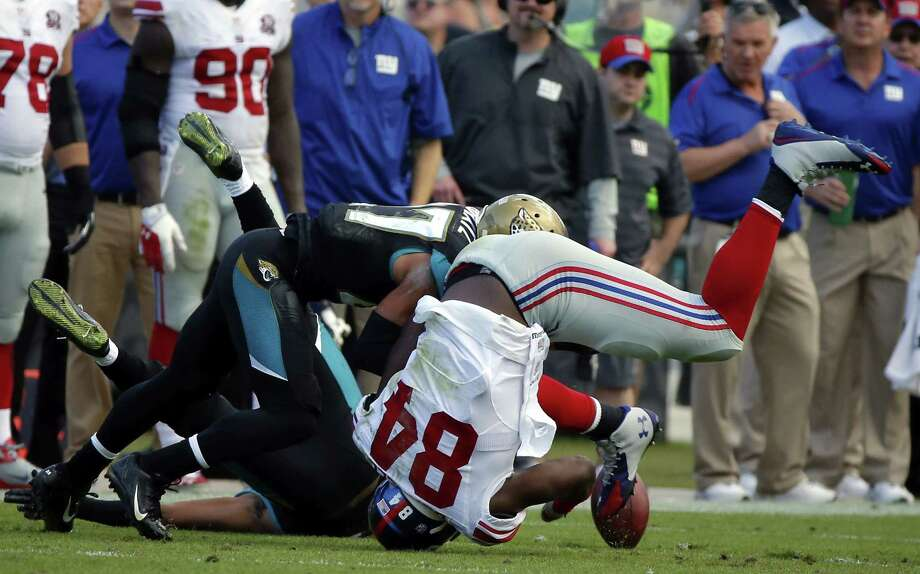 Stephen B. Morton — The Associated Press  Giants tight end Larry Donnell (84) fumbles the ball after being hit by Jaguars cornerback Dwayne Gratz during the second half Sunday. Photo: AP / FR56856 AP
