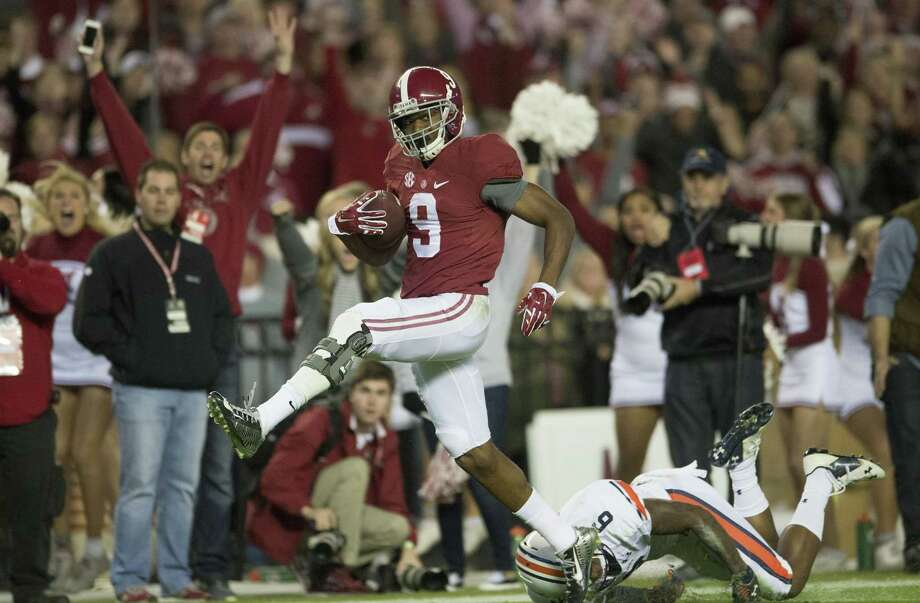 Alabama wide receiver Amari Cooper (9) scores on a 75-yard touchdown reception as Auburn defensive back Jonathon Mincy (6) attempts to tackle him Saturday. Photo: The Associated Press   / The Montgomery Advertiser