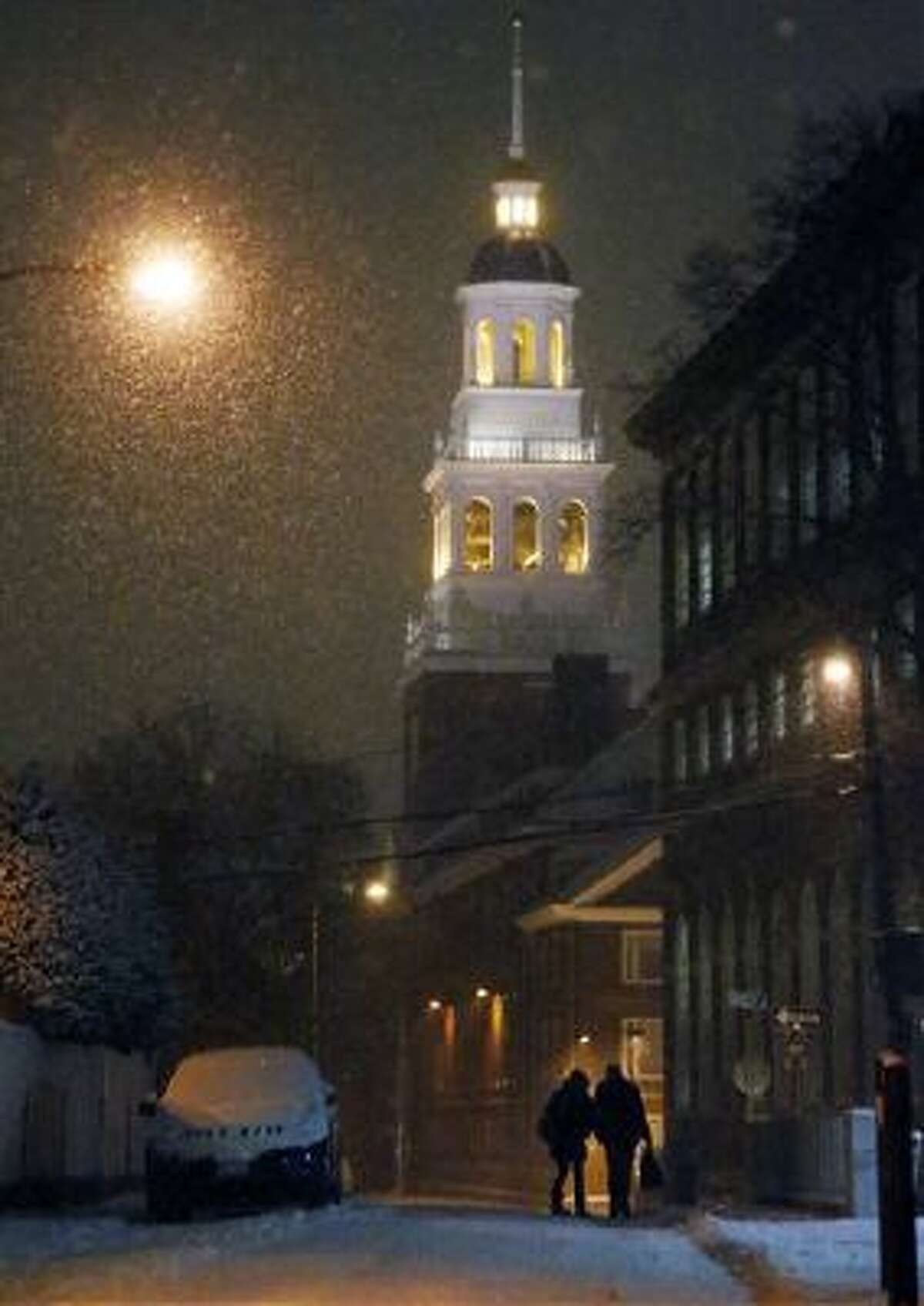 A couple walk as snow falls in Harvard Square in Cambridge, Mass., on Tuesday.