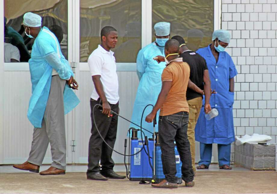 In this photo taken on Saturday, March 29, 2014, medical personnel at the emergency entrance of a hospital receive suspected Ebola virus patients in Conakry, Guinea. Senegal has closed its land border with neighboring Guinea to prevent the spread of the Ebola outbreak, which has killed at least 70 people. Senegal's Interior Ministry announced the border closure Saturday. It also said officials in the southern region of Kolda closed a weekly market which draws thousands of people from the neighboring West African countries of Guinea, Gambia and Guinea-Bissau. Guinea confirmed last week that several victims of hemorrhagic fever in the country's southern region had tested positive for Ebola. (AP Photo/ Youssouf  Bah) Photo: AP / AP