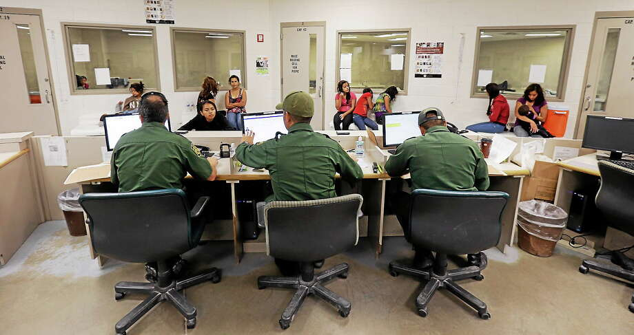 This June 18, 2014 photo shows U.S. Customs and Border Protection agents working at a processing facility in Brownsville,Texas. Photo: AP Photo/Eric Gay, Pool   / AP (POOL)