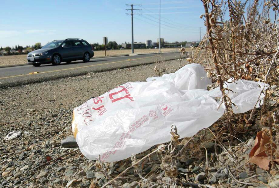 FILE-In this file photo taken Friday, Oct. 25, 2013, a plastic shopping bag liters the roadside in Sacramento, Calif. Gov. Jerry Brown has signed legislation on Tuesday, Sept. 30, 2014 imposing the nation's first statewide ban on single-use plastic bags.  (AP Photo/Rich Pedroncelli) Photo: AP / AP