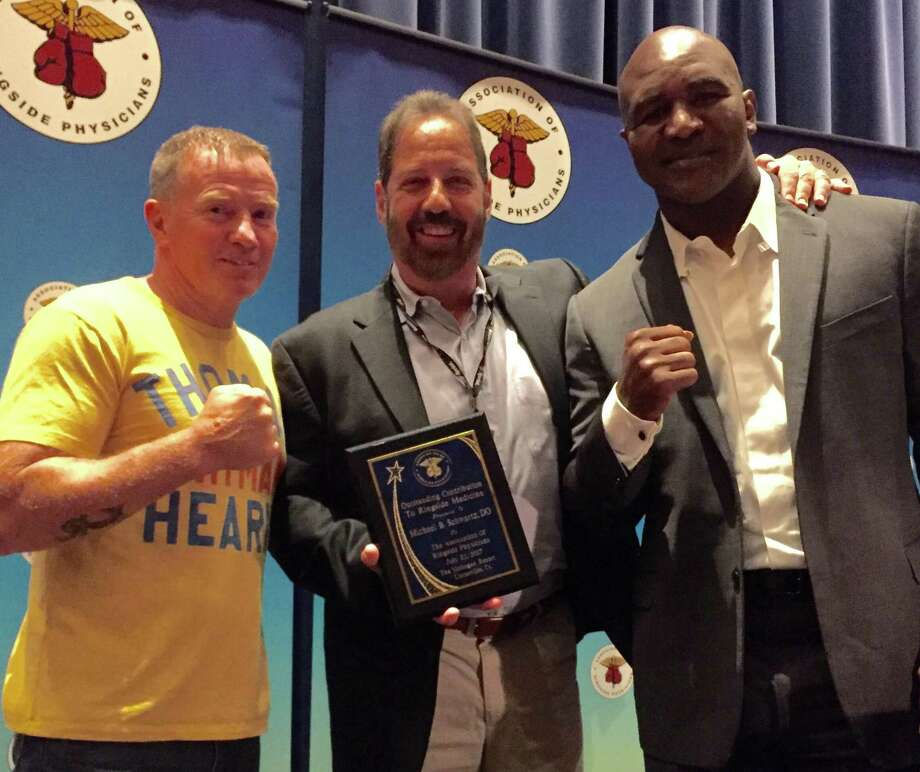 Dr. Michael Schwartz, center flanked by Evander Holyfield, right and Micky Ward at at the Association of Ringside Physician gala at Mohegan Sun Casino on July 22. Schwartz was honored for his contributions to ringside medicine. Photo: /