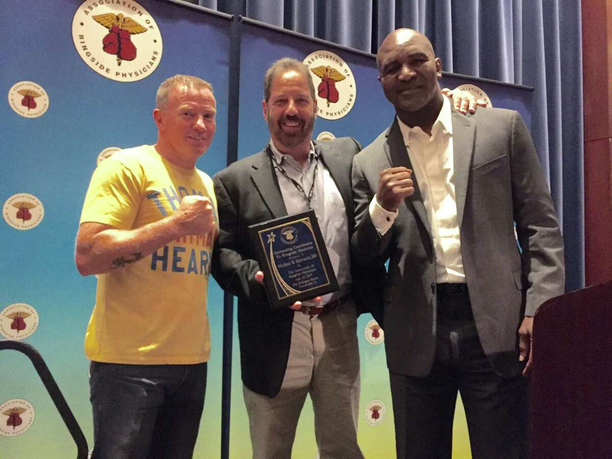 Dr. Michael Schwartz, center flanked by Evander Holyfield, right and Micky Ward at at the Association of Ringside Physician gala at Mohegan Sun Casino on July 22. Schwartz was honored for his contributions to ringside medicine.