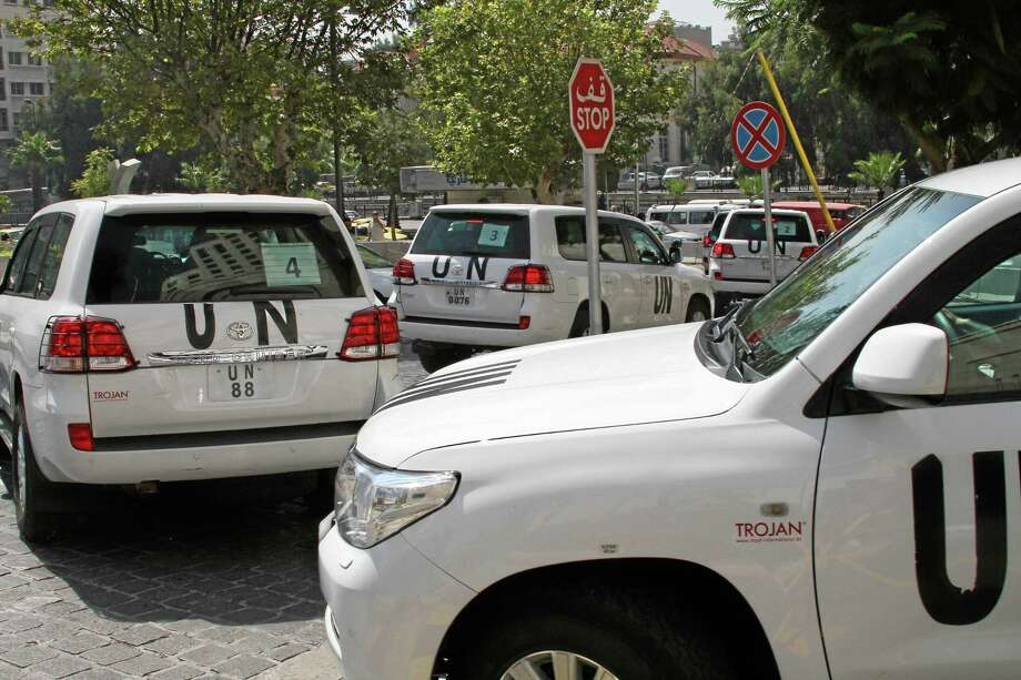 FILE -- In this August 26, 2013, file Photo, a U.N. team, that is scheduled to investigate an alleged chemical attack that killed hundreds last week in a Damascus suburb, leaves their hotel in a convoy, in Damascus, Syria. In a  statement issued Tuesday, May 27, 2014, by the chemical weapons watchdog that is overseeing the dismantling of Syria's chemical weapons program, said a convoy of its inspectors has come under attack, but all are safe.  The Organization for the Prohibition of Chemical Weapons said that the inspectors had been traveling to the site of an alleged chlorine gas attack site when they were attacked. (AP Photo, File) Photo: AP / AP