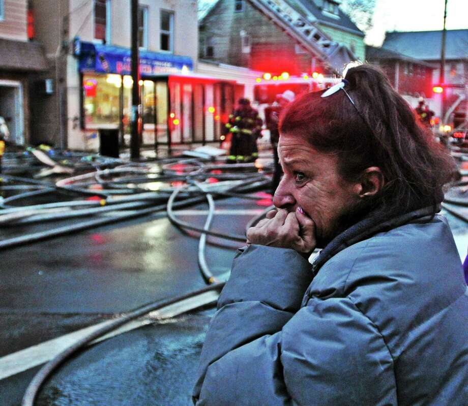 Carmella Stankiewicz watches as firefighters battle a two-alarm blaze at 95 Farren Ave. in New Haven Friday. Stankiewicz, a neighbor, had gone into the building to help get people out and was worried one of the residents had gone back in. Photo: Peter Casolino — New Haven Register