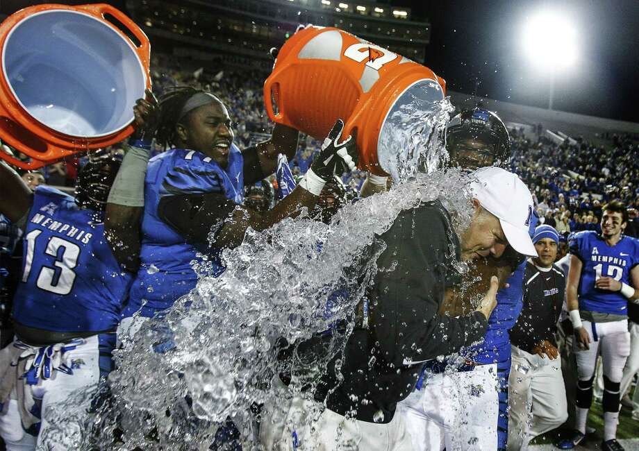 Memphis head coach Justin Fuente, right, is doused with water after the Tigers beat UConn 41-10 Saturday to clinch a share of the AAC title. Photo: Mark Weber — The Associated Press   / The Commercial Appeal
