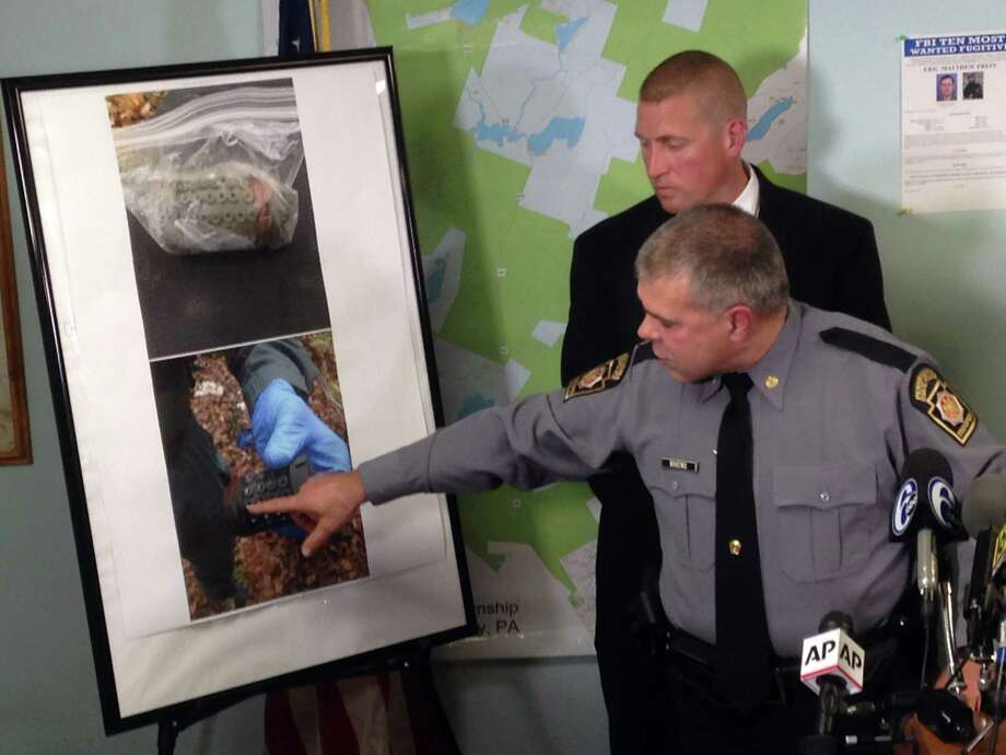 Lt. Col. George Bivens points to images of the pipe bombs that police say were left by trooper ambush suspect Eric Frein in the Pennsylvania woods, at a news conference in Blooming Grove Pa., Tuesday Sept. 30, 2014.  (AP Photo/Michael Rubinkam) Photo: AP / AP