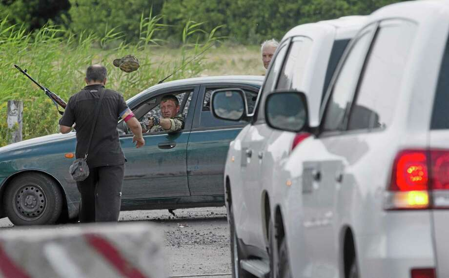A pro-Russian rebel throws a hat to his comrade to keep uniform formality as the convoy of the OSCE mission in Ukraine approaches to a check-point near the village of Rassipne, near the scene of the Malaysia Airlines plane crash, Donetsk region, eastern Ukraine, Thursday, July 31, 2014. (AP Photo/Dmitry Lovetsky) Photo: AP / AP