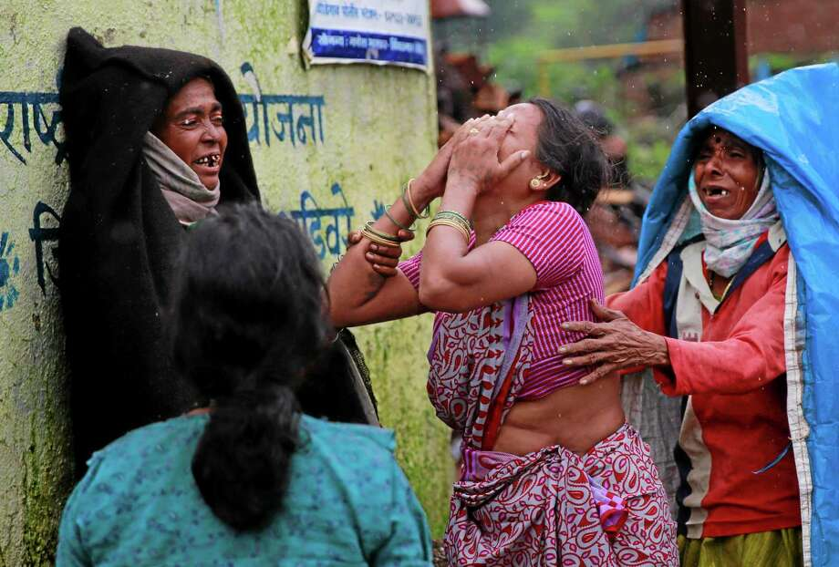 Relatives wail after seeing the body of a victim after a massive landslide in Malin village in Pune district of western Maharashtra state, India, Thursday, July 31, 2014. Two days of torrential rains triggered the landslide early Wednesday, killing more than two dozen people and trapping more than 150, authorities said. (AP Photo/Rafiq Maqbool) Photo: AP / AP