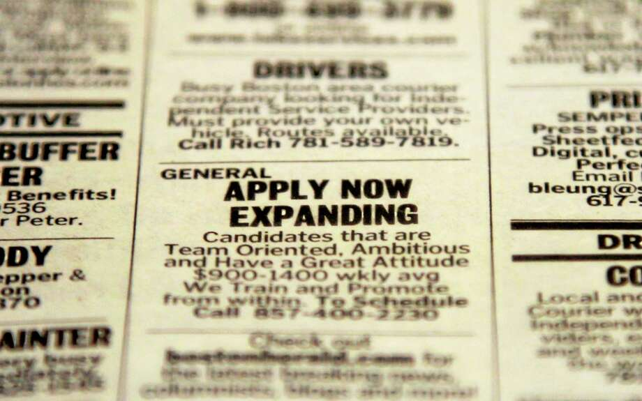 FILE - In this Tuesday, Dec. 11, 2012 file photo, an advertisement in the classified section of the Boston Herald newspaper calls attention to possible employment opportunities in Walpole, Mass. The year 2013 marked a third straight year of modest job growth of 2.1 to 2.2 million jobs,  still too few to restore all the jobs lost to the Great Recession, which officially ended more than 4½ years ago.  (AP Photo/Steven Senne, File) Photo: AP / AP