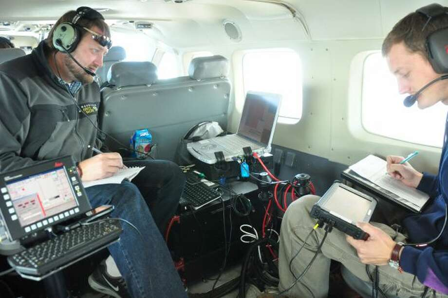 In this photo taken in October 2012, released by WSI, a Quantum Spatial Company, sensor operators Lennie Rummel left, and Drew Wendeborn, right, are shown inside a helicopter taking measurements with LIDAR, a high-tech laser system mounted on the aircraft, to build a detailed elevation map of the terrain above Omak, Wash. The maps can be used by planners and homeowners to begin to assess landslide risk. (AP Photo/ WSI, a Quantum Spatial Company) Photo: AP / WSI, A Quantum Spatial Company